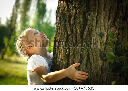 Little girl hugging a tree, looking up - stock photo
