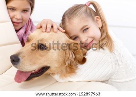 Little girl hugging golden retriever with love, older sister in background. - stock photo