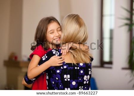 little girl hugging her mother at home - stock photo