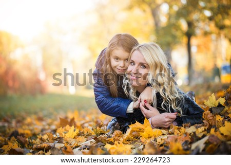 little girl hugging her mother lying in the autumn park - stock photo
