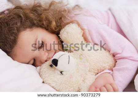 Little girl hugging her teddy while sleeping - stock photo
