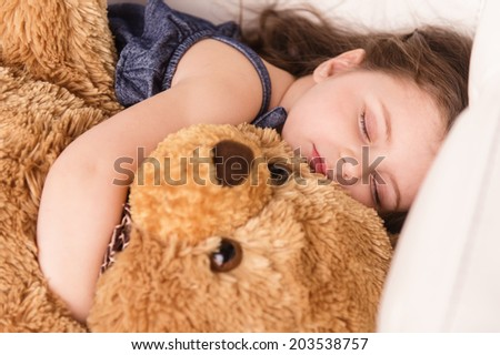 little girl hugging teddy bear. closeup view of nice girl sleeping - stock photo