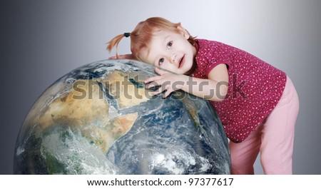 Little girl hugs with love the Earth globe - stock photo