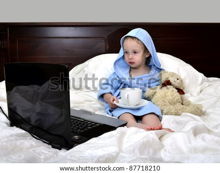 little girl in a bathrobe relaxing on the bed after a shower with cup of tea and laptop - stock photo