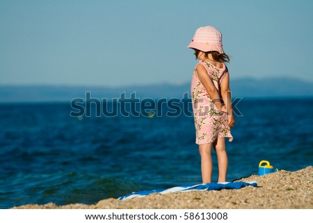 Little girl in a beautiful dress standing on the beach and looks into the distance. - stock photo