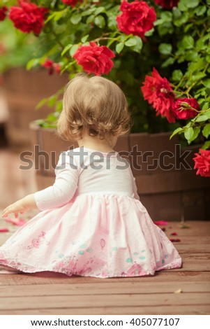 Little girl in a beautiful pink dress sits near red roses bush. Back view. - stock photo
