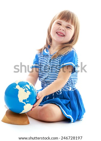 Little girl in a blue dress sitting on the floor and turns the globe.concept childhood education and child development.Isolated on white background - stock photo