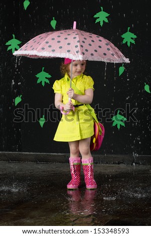 Little girl in a bright yellow dress and rubber boots with pink umbrella in hands - stock photo