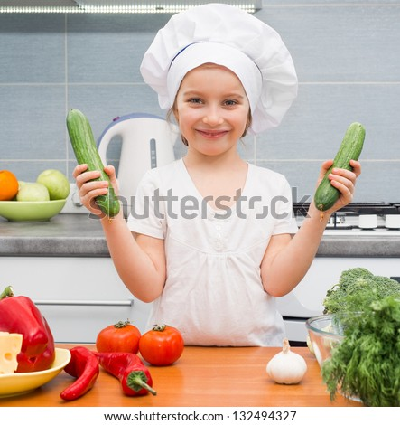 little girl in a cap chef in the kitchen with cucumbers - stock photo