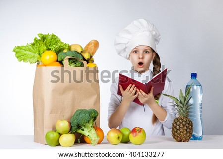 Little girl in a cap cook a variety of fresh food. Girl holds red book in hands. Wonder human emotion, facial expression Fehling. Menu. Cooking food - stock photo