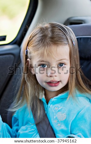 Little girl in a car seat looking at the viewer. - stock photo