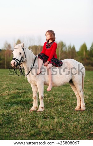 Little girl in a dress sitting on a white horse and looks into the distance Outdoors - stock photo