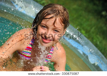 Little girl in a inflatable pool. Summer outdoor. - stock photo