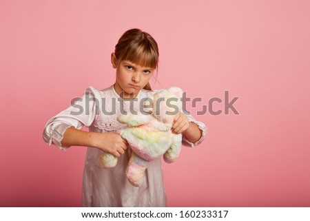 Little girl in a nightgown abusing her teddy bear - stock photo