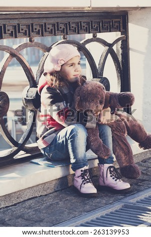 little girl in a pink beret sits at a fencing and holds a toy bear in hand - stock photo