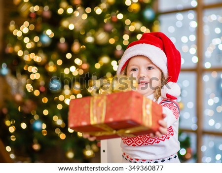 Little girl in a red Christmas hat gives a gift - stock photo