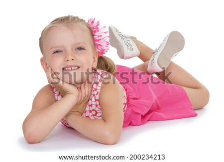 little girl in a red dress lies with his legs crossed on a white background - stock photo