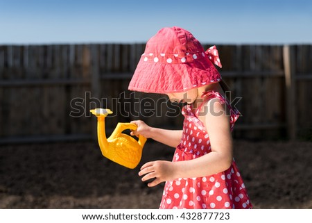 Little girl in a red spotted dress and hat with a yellow toy watering-can in the garden. The day is sunny and the shadow are deep. - stock photo