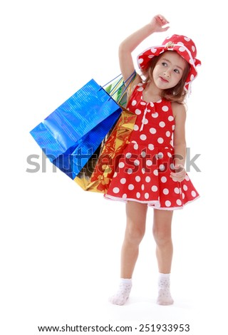 little girl in a summer dress with polka dots is on the shoulder of shopping bags.Isolated on white background, Lotus Children's Center. - stock photo