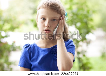 Little girl in a summer park talking on the phone, in a blue dress. Blonde - stock photo