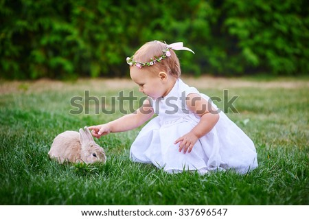 little girl in a white dress plays with a rabbit in the park. - stock photo