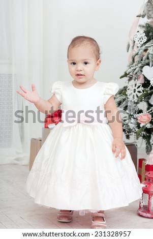 Little girl in a white dress  stand near a Christmas fir-tree - stock photo