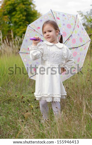 little girl in a white dress stands with an umbrella in the autumn meadow - stock photo
