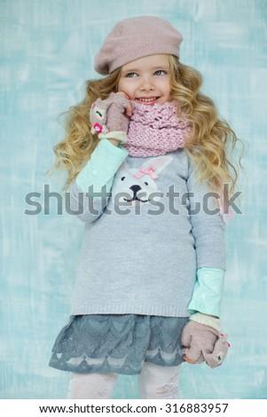 Little girl in a winter cap wool scarf little fashion portrait - stock photo