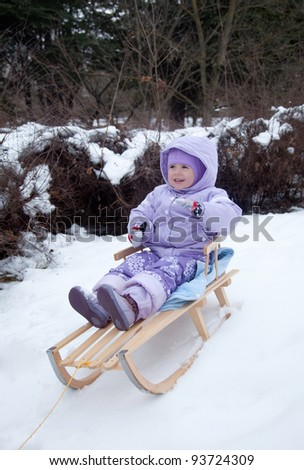 little girl  in a winter park on a sled - stock photo