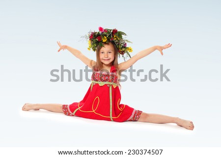 Little girl in a wreath sitting on the splits. - stock photo