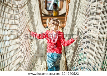 Little girl in amusement park rope tunnel - stock photo