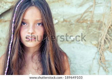 Little girl in an summer setting smiles at the camera. - stock photo
