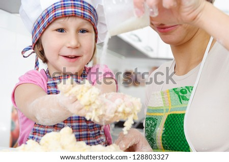 Little girl in baker hat and apron cooking in kitchen with mother - stock photo