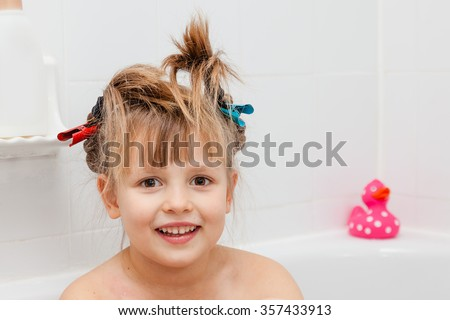 Little girl in bathroom ready to wash the body, but not hair. Long hair put together with hair clips for not being wet. Selective focus on girls eyes. - stock photo