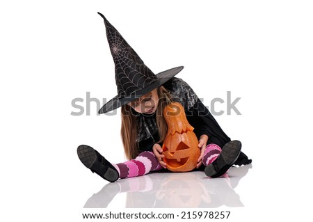 Little girl in black hat with pumpkin sitting on floor, isolated on white background - stock photo