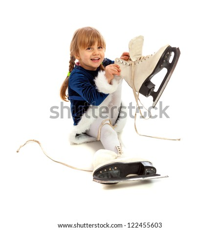Little girl in blue dress smiling and putting on big skates isolated on white - stock photo