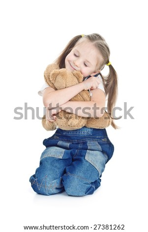 little girl in blue jeans seats hugging with toy bear - stock photo