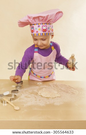 Little girl in chef hat and tablier with classic wooden rolling pin, dough and flour. Gastronomy and culinary cooking. - stock photo