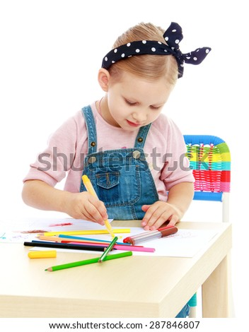 Little girl in denim overalls and a bandage on his head draws with markers at the table-isolated on white background - stock photo