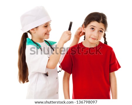 Little girl in doctor costume are inspecting the another girl's ears with magnifier, isolated on white - stock photo