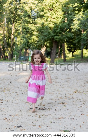 Little girl in dress runs on the sand at the camera smiling - stock photo