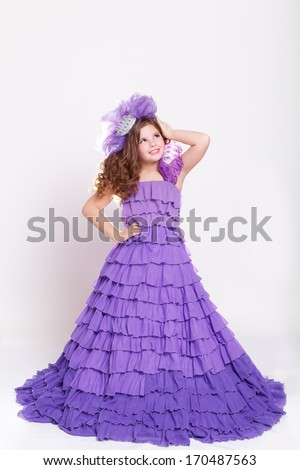 Little girl in fashion purple dress, Glamour little child girl wearing fairy violet costume. Kid fashion. Vogue style. Isolate, studio, white background. Child portrait in fantasy dress.  - stock photo