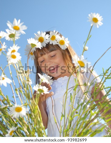 Little girl in field of beautiful summer flowers - stock photo
