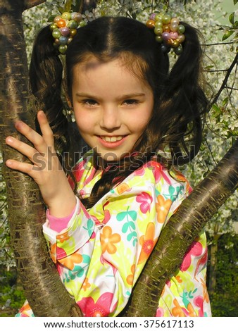 Little girl in garden standing near the apple tree - stock photo