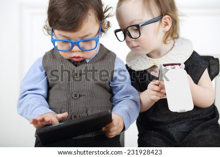 Little girl in glasses and black dress with mobile phone next to serious boy with tablet computer - stock photo