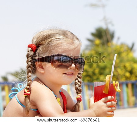 Little girl in glasses and red bikini on playground drink  juice. - stock photo