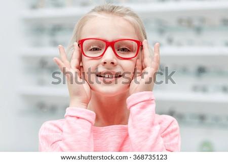 little girl in glasses at optics store - stock photo