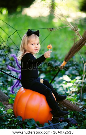 little girl in halloween costume eat sweet tricks with jack pumpkin - stock photo