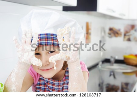 Little girl in hat and apron cooking in kitchen - stock photo