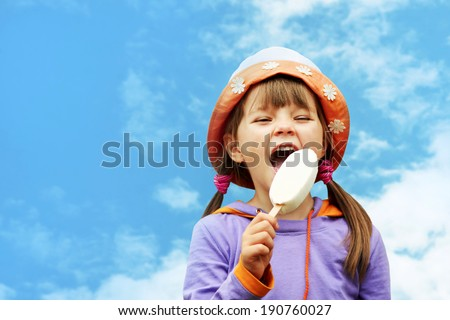little girl in hat eating ice cream on a background of sky - stock photo